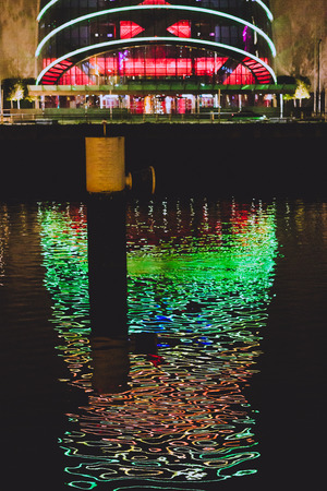 DUBLIN, IRELAND - December 27th, 2018: the Convention Centre in Dublin with red and green Christmas lighting and reflection on the river Liffey Sajtókép