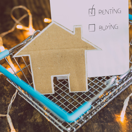 miniature house made of cardboard in shopping basket with renting text ticked, concept of buying or selling a property