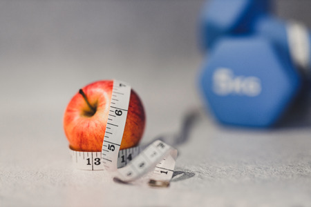 health and fitness resolutions, heavy dumbbells on concrete surface with measuring tape and apple