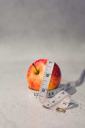 healthy diet concept, red apple with measuring tape around it Reklamní fotografie