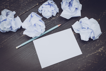 pencil on desk with notepad and scrunched paper balls, concept of drafting and struggling to write documents