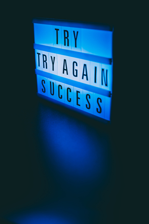 try try again success message on lightbox in the dark, motivational concept