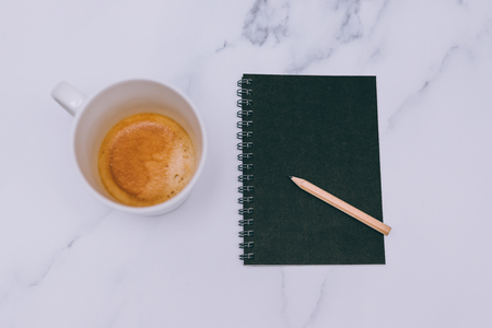 flatlay of mini spiral notebooks with pencil and cup of coffee on marble desk shot from a top down perspective