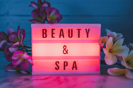 beauty and spa lightbox text surrounded by tropical frangipani monoi flowers Standard-Bild