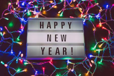 lightbox with Happy New Year message surrounded by colorful fairy lights, concept of nye party and celebrations
