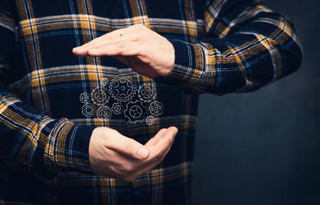 man with gearwheel mechanism design between his hands, with flannel shiirt and dark background Standard-Bild - 117449054