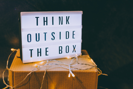 Think outside the box message on lightbox on top of closed parcel with fairy led lights, concept of being unique for success