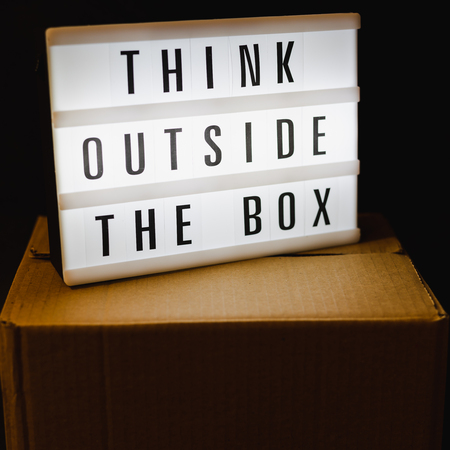 Think outside the box message on lightbox on top of closed parcel, concept of being unique for success Banque d'images - 117449083