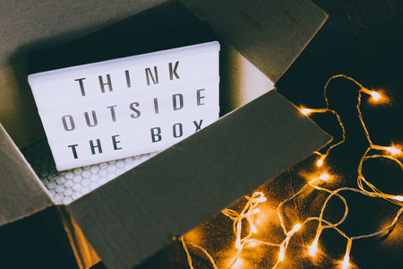 Think outside the box message on lightbox coming out of a parcel with fairy led lights, concept of being unique for success