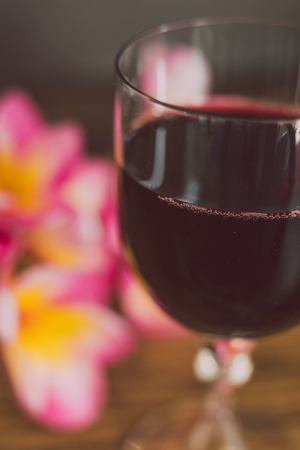 close-up of glass of intensely coloured red wine and tropical Australian flowers on wooden table, concept of elegant or expensive wine choices 版權商用圖片
