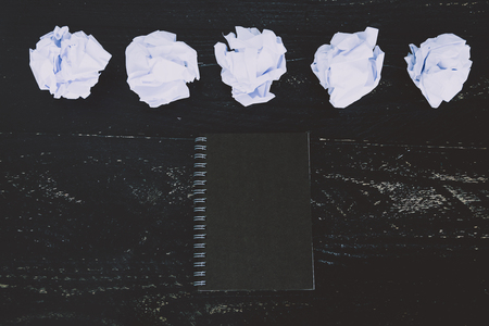 concept of drafting documents and struggling to write a text, set of scrunched paper balls and empty notepad on dark moody background