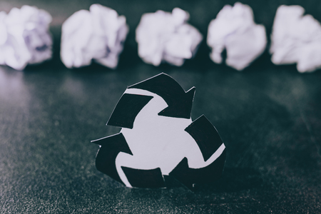recycle symbol surrounded by scrunched paper balls, concept of reducing damage to the environment Stockfoto