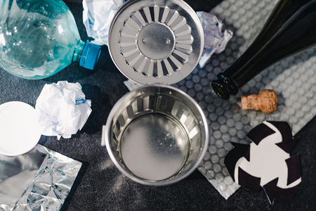 open empty trash can surrounded by reusable waste materials like plastic paper and glass with recycle symbol, concept of reducing damage to the environment Stock Photo