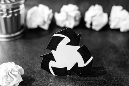 recycle symbol surrounded by scrunched paper balls with garbage bin, concept of reducing damage to the environment
