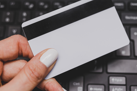 woman's hand holding payment card with laptop keyboard in the background, concept of online shopping and purchases Stock fotó