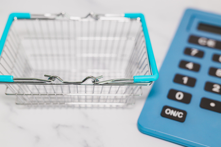 empty shopping basket and huge calculator in the background, concept of shopping budget