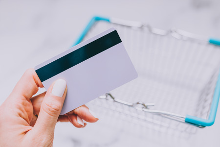 womans hand holding payment card and empty shopping basket, concept of shopping and expenses