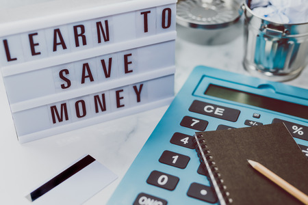lightbox with Learn to save money message next to payment card calculator and stationery on marble desk, concept of learning to spend less and refrain from excessive shopping
