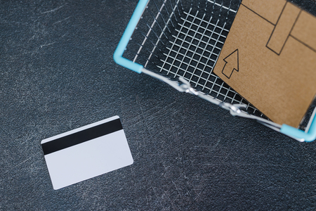 shopping cart with cardboard parcel email envelope and payment card on concrete desk, concept of shipping and tracking your online deliveries Reklamní fotografie