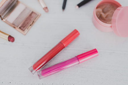 Colorful lipglosses surrounded by other make-up products on wooden desk, concept of beauty industry Stock Photo