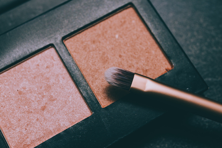 natural toned bronzers eyeshadows and highlighters  with brush on dark background, concept of make-up and cosmetics industry trends