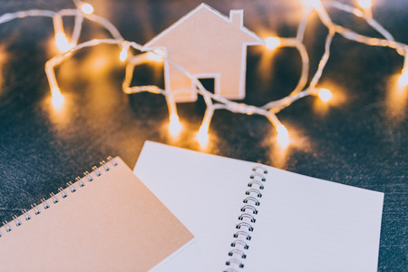 miniature house made of cardboard with fairy lights and notebooks with copyspace, concept of planning to buy renovate or move house