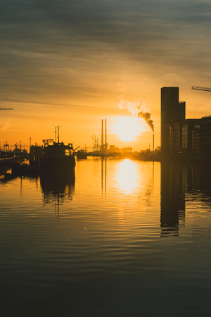 DUBLIN, IRELAND - February 28th, 2019: gold toned sunrise over Dublin Bay and the docklands with cityscape including the Poolbeg Chimneys