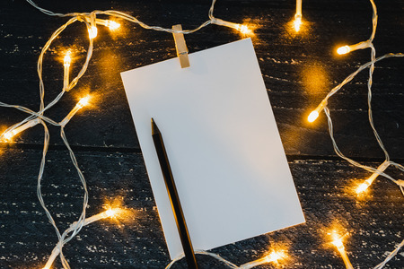 notepad and pencil on wooden desk with copyspace to add you text surrounded by fairy lights, concept of sharing a message