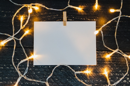 notepad on wooden desk with copyspace to add you text surrounded by fairy lights, concept of sharing a message