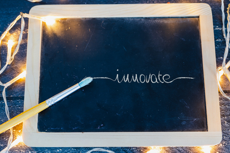 brush and blackboard on wooden desk with text Innovate surrounded by fairy lights, concept of sharing a message Stock Photo