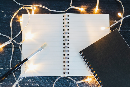 notebooks and brush on wooden desk with copyspace to add you text surrounded by fairy lights, concept of artist and inspiration