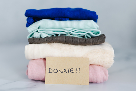 decluttering and tidying up concept: piles of tshirts and clothes being sorted into Keep Discard and Donate categories Stock Photo
