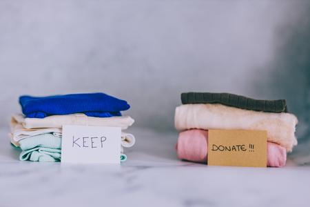 concetto di decluttering e riordino: pile di magliette e vestiti smistati nelle categorie Keep Scarta e Dona Archivio Fotografico