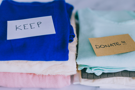 decluttering and tidying up concept: piles of tshirts and clothes being sorted into Keep Discard and Donate categories Stock fotó