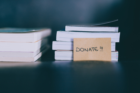 decluttering and tidying up concept: selecting which books to keep and which to discard or donate