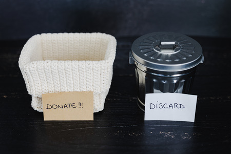 decluttering and tidying up concept: storage basket and gargabe bin to select which items to keep and which to discard