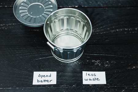 ecology and consumerism concept: spend better for less waste garbage bin with text