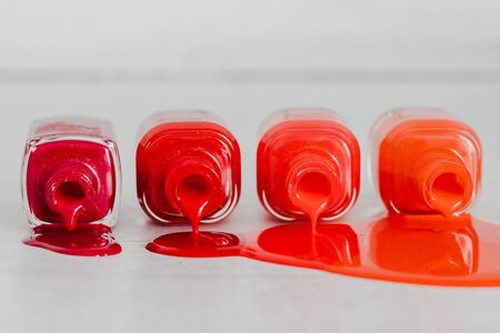 nail polish bottles in different shades of red to orange and purple spilling color on wooden surface, concept of cosmetics industry and manicure 写真素材 - 131754317