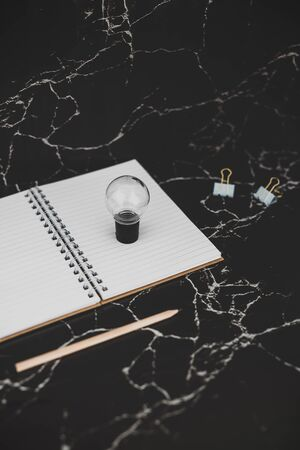 idea lightbulb and empty notebook to write goals and plans, concept of potential and achievements Stock Photo