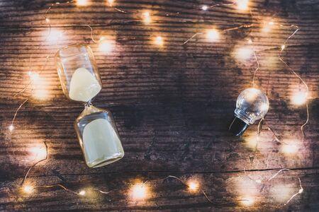 Es hora de nuevas ideas flatlay conceptual con reloj de arena y bombilla rodeada de luces de colores bokeh en un escritorio de oficina de madera