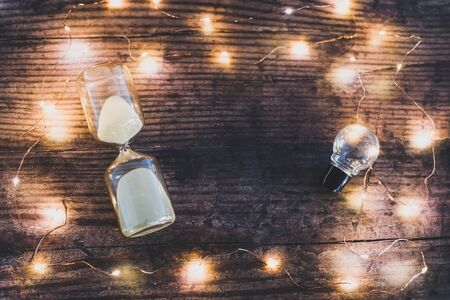 time for new ideas conceptual flatlay with hourglass and lightbulb surrounded by fairy lights bokeh on wooden office desk