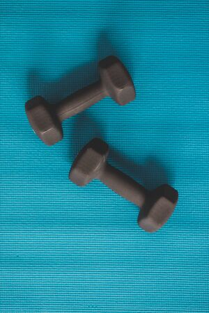 black set of dumbbells on blue yoga mat, concept of keeping fit with home exercises