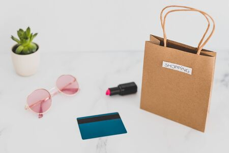 shopping bag on marble table top with mix of daily and stylish items around it and payment card, shot at shallow depth of field with soft muted tones