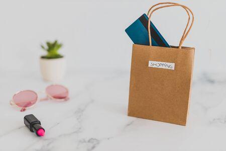 borsa per la spesa sul piano del tavolo in marmo con un mix di oggetti quotidiani ed eleganti intorno e carta di pagamento, ripresa a profondità di campo ridotta con toni tenui e tenui
