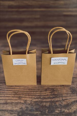 shop bags with crazy and intentional shopping labels, concept of consumerism vs minimalism Stock Photo