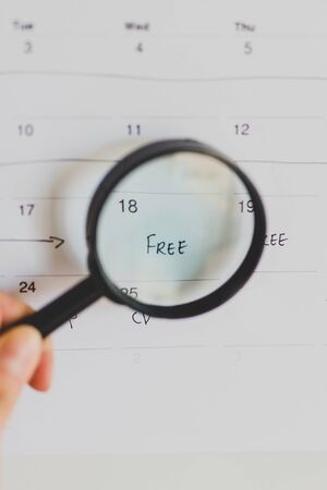hand holding magnifying glass over a day marked as free on the calendar, concept of time management