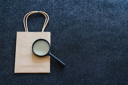 shopping bag and magnifying glass analyzing it on black glitter background, customer spending habits concept Archivio Fotografico