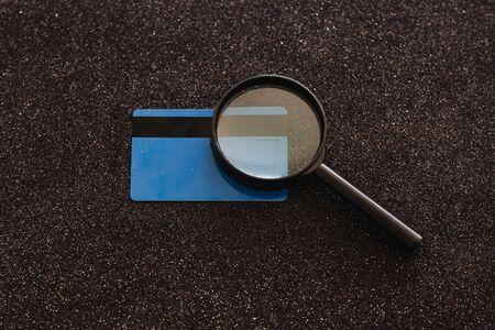 tarjeta de pago y lupa analizándolo sobre fondo negro brillo, concepto de hábitos de gasto del cliente Foto de archivo