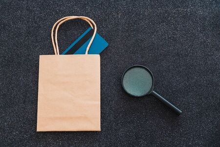 shopping bag with payment card and magnifying glass next to them, customer spending habits concept