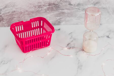pink shopping basket with hourglass and fairy lights, concept of flash sales and temporary deals
